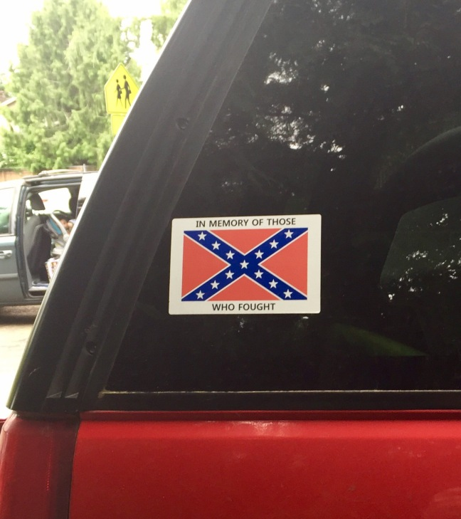 "A vehicle near a school displays a Battle Flag decal saying ""In memory of those who fought."""